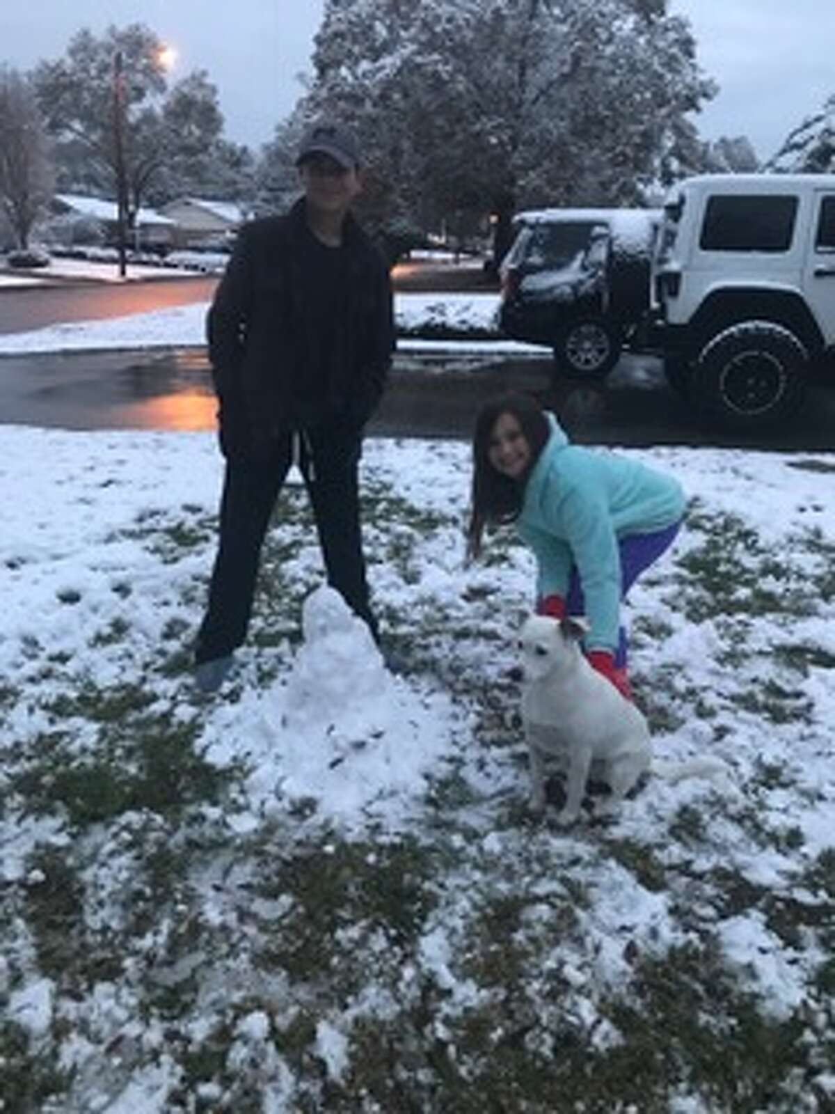 Bella is clearly supervising her humans as they build a yard snowman. Photo by Visa Robison.