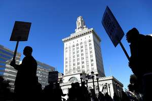 OAKLAND, CA - DECEMBER 05:  Oakland city workers carry signs as they picket outside of Oakland City Hall on December 5, 2017 in Oakland, California. Thousands of Oakland city workers went on strike early Tuesday as contract negotiations stalled out following the expiration of the unions� contract in July.  (Photo by Justin Sullivan/Getty Images)