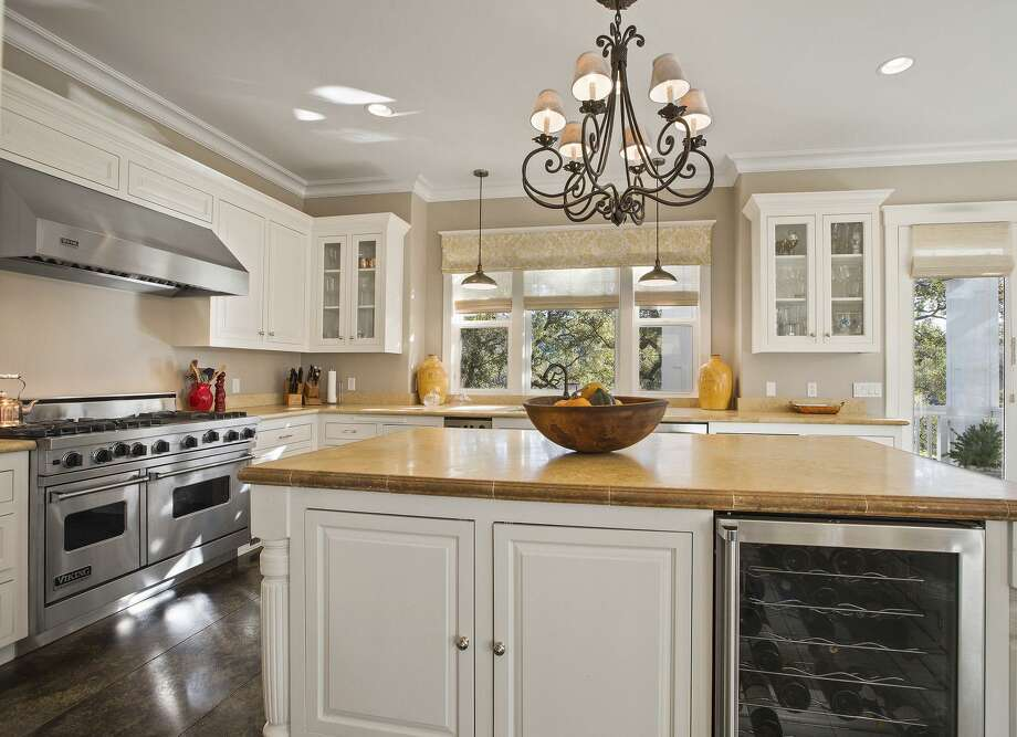 The kitchen hosts professional appliances and access to a side deck. / ONLINE_CHECK
