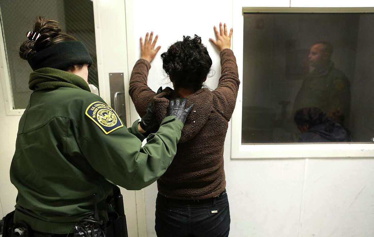 Border Patrol agent Tahlia Leyva, left, frisks a woman from Guatemala during processing in the Marfa office in the Big Bend Sector, which includes Van Horn where Rogelio Martinez worked and died while on patrol.