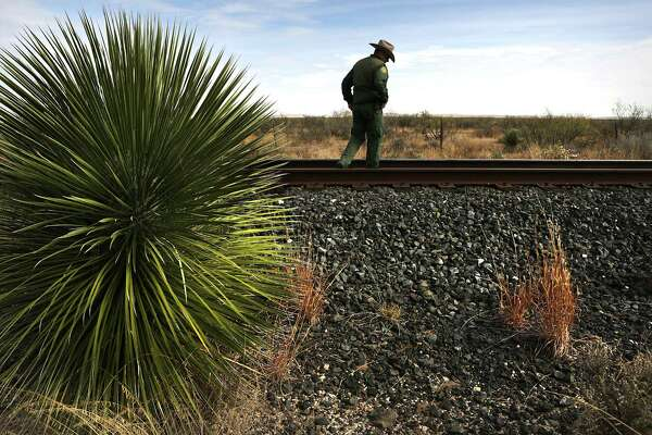 Border Patrol Supervisor Shane Jahn walks along train tracks checking for foot prints west of Marfa, Tx in the Big Bend Sector on Tuesday, Dec. 5, 2017.