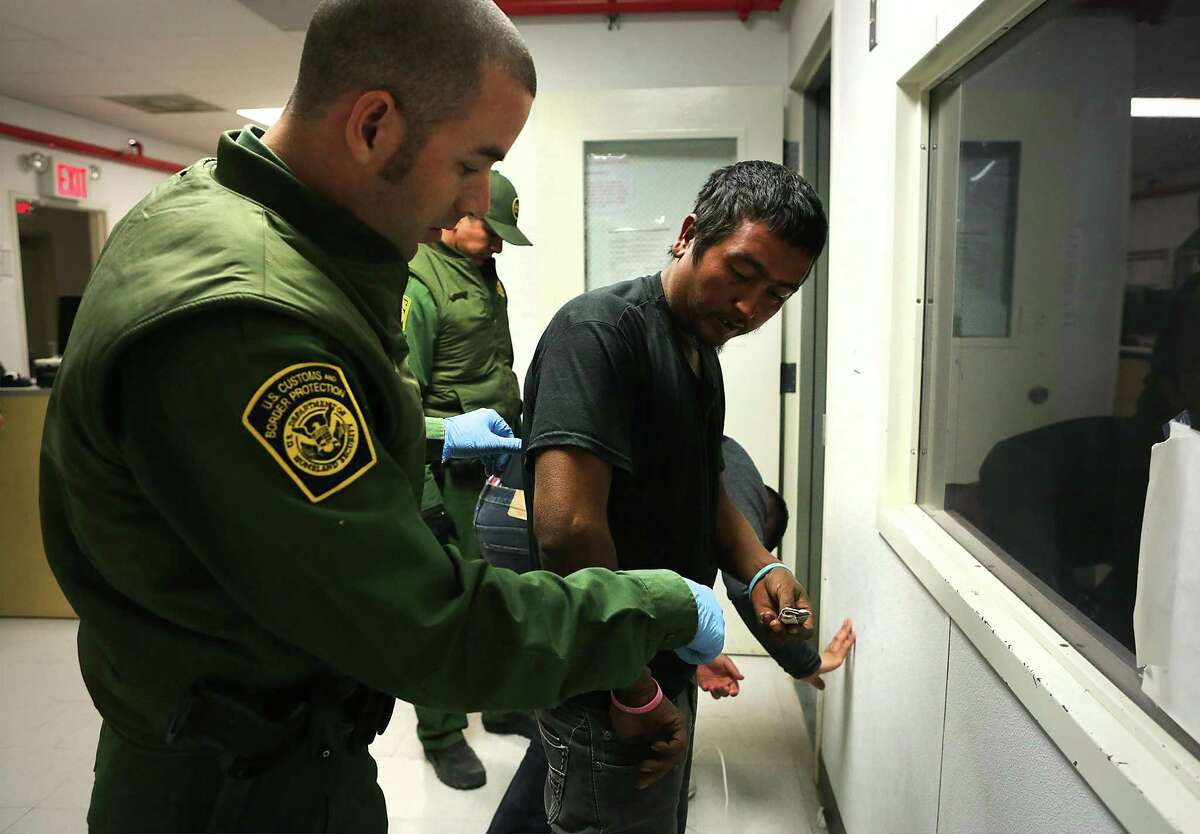Border Patrol agent Ben Giroux, left, processes a man from Mexico in the Marfa office in the Big Bend Sector, which includes Van Horn where Rogelio Martinez worked and died while on patrol.
