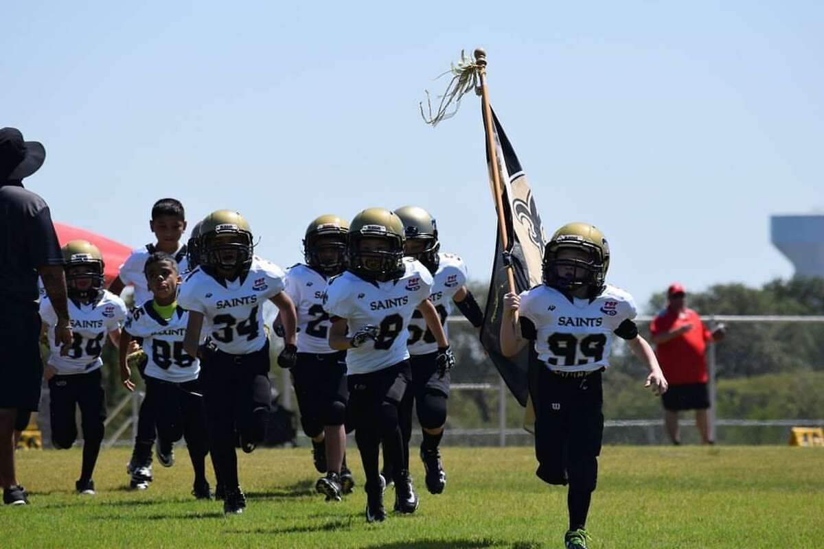 The San Antonio Saints, a youth football team, take the field prior to game.