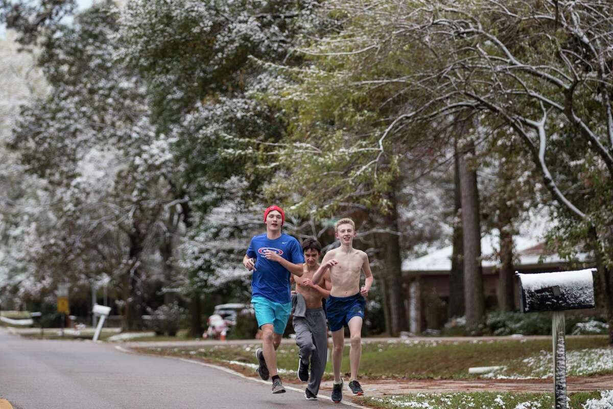 A trio of runners run under snow-covered trees during a workout for the Oak Ridge High School cross country team after the area saw snow fall overnight on Friday, Dec. 8, 2017, in Oak Ridge North, Texas.