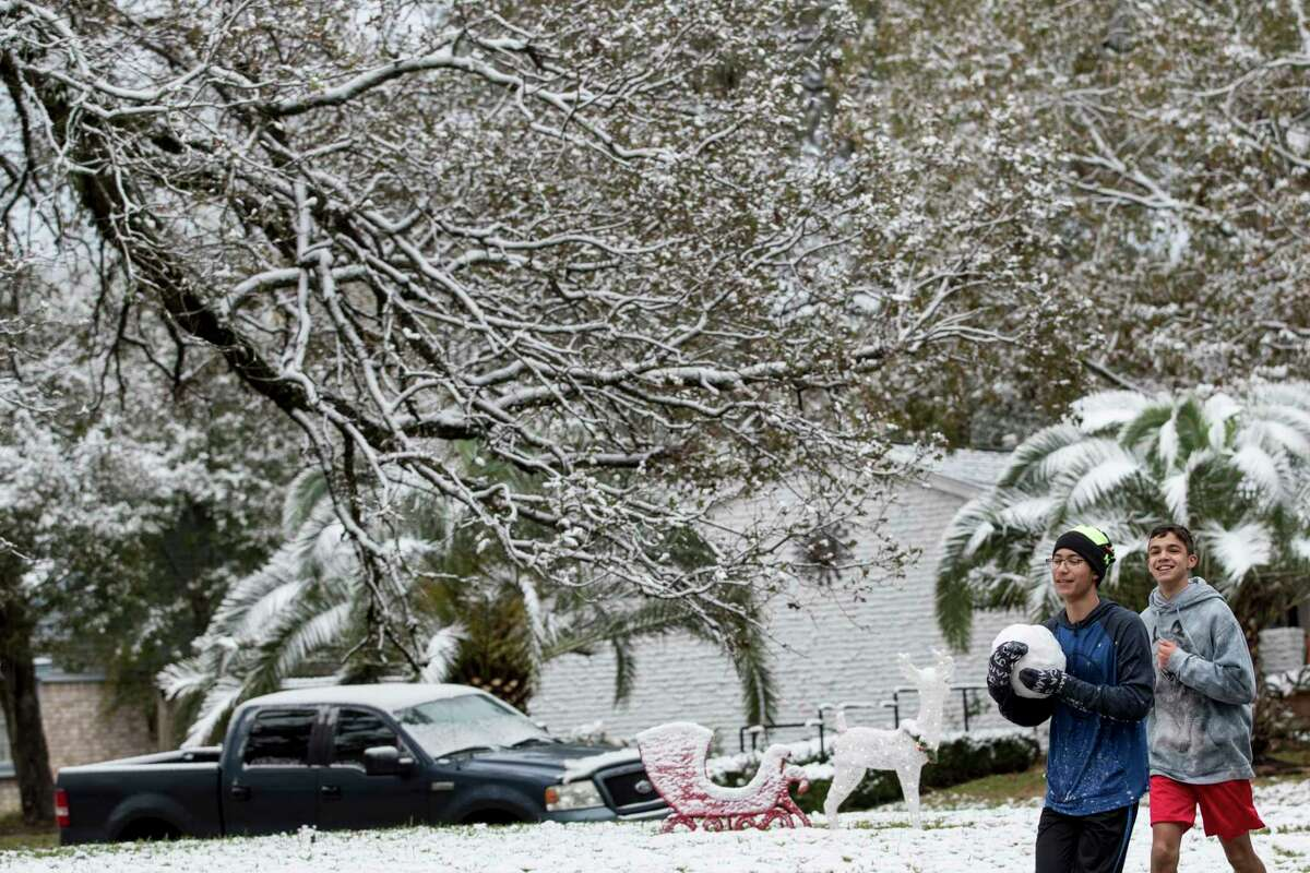 Tyler Hammett carries a large snowball as he and Noah Garcia run under snow-covered trees after the area saw snow fall overnight on Friday, Dec. 8, 2017, in Oak Ridge North, Texas.