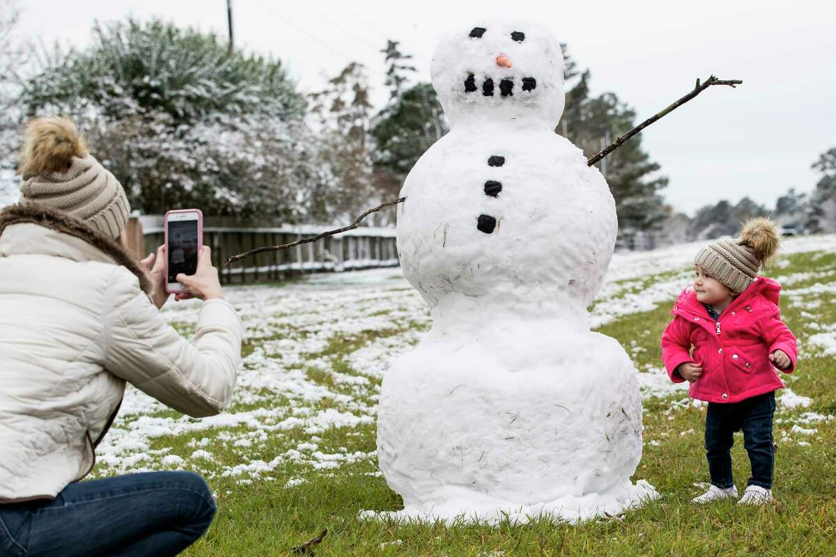 After a rare Houston snowfall, Jordan Rogatchev, left, takes a photo of her daughter, Amelia next to a snowman.