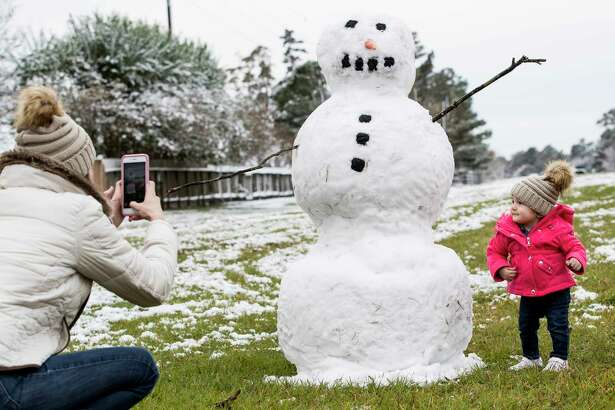 Jordan Rogatchev, left, takes a photo of her daughter, Amelia next to a snowman built after the area saw snow fall overnight on Friday, Dec. 8, 2017, in Spring.