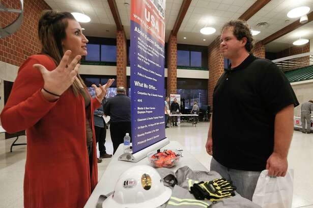 In this Thursday, Nov. 2, 2017, photo, a recruiter from a driller in the shale gas industry, left, speaks with an attendee at a job fair in Cheswick, Pa. On Friday, Dec. 8, 2017, the U.S. government issues the November jobs report. (AP Photo/Keith Srakocic)