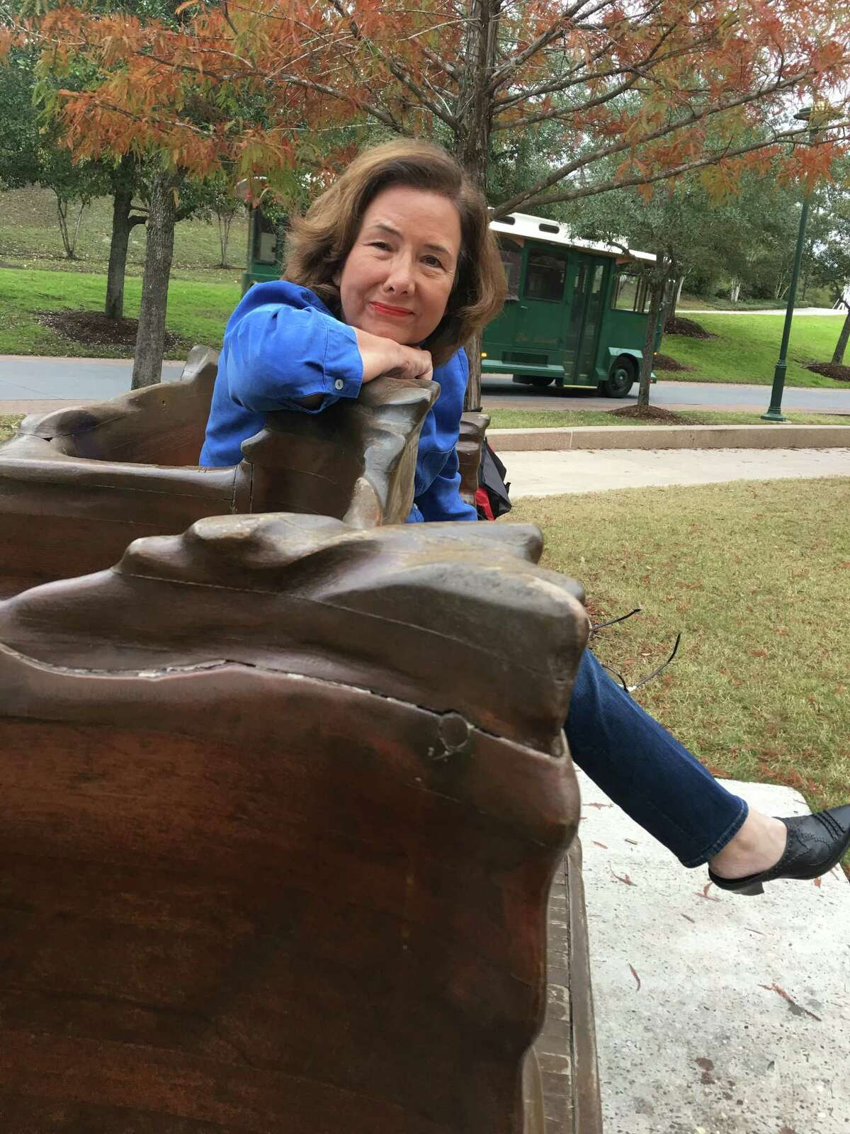"""Woodlands resident Amy Lecocq sitting on Bob MosierÂ?'s Â?""""Hail and Farewell Henry MooreÂ?"""" art bench on The Woodlands Waterway near Town Green Park."""