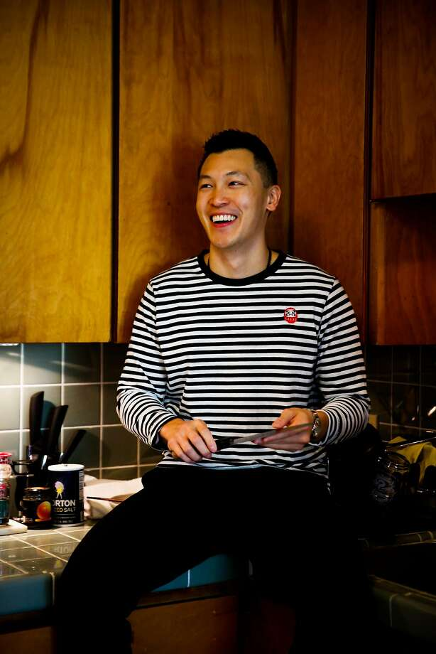 Daniel Situ sits on the counter of his kitchen in his S.F. apartment. Photo: Gabrielle Lurie, The Chronicle