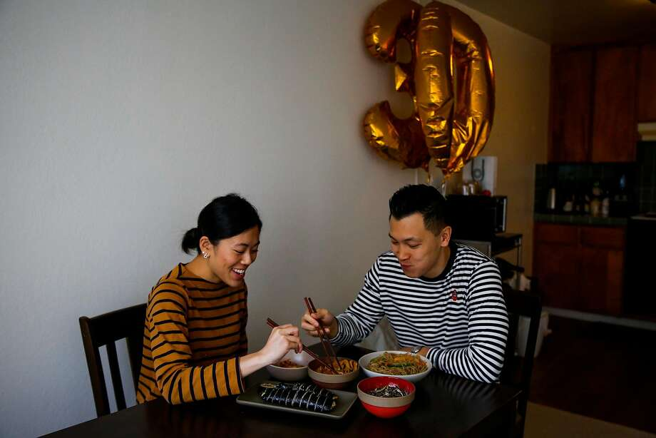 Daniel Situ and his girlfriend, Christine Au-Yeung, share a meal in their S.F. apartment. Photo: Gabrielle Lurie, The Chronicle