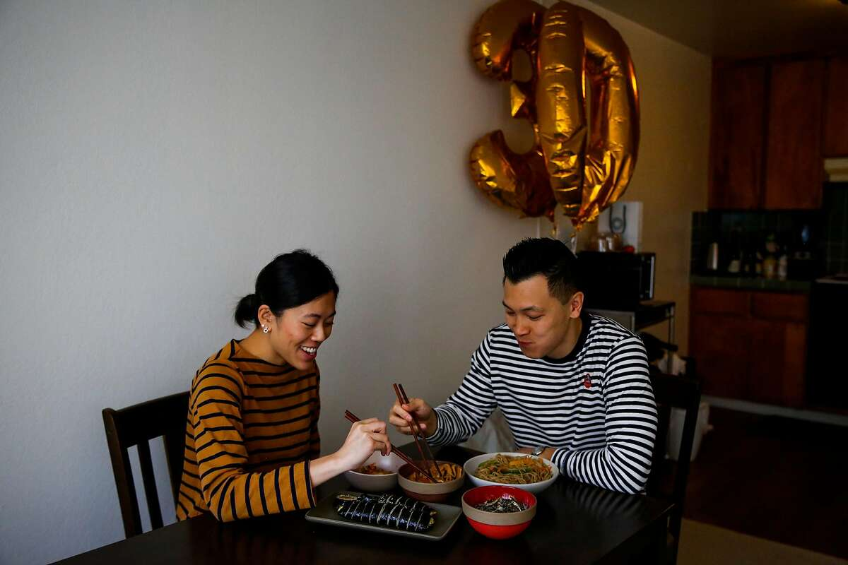 (l-r) Christine Au-Yeung and her boyfriend Daniel Situ eat breakfast in their apartment in San Francisco, Calif., on Sunday, Dec. 3, 2017.