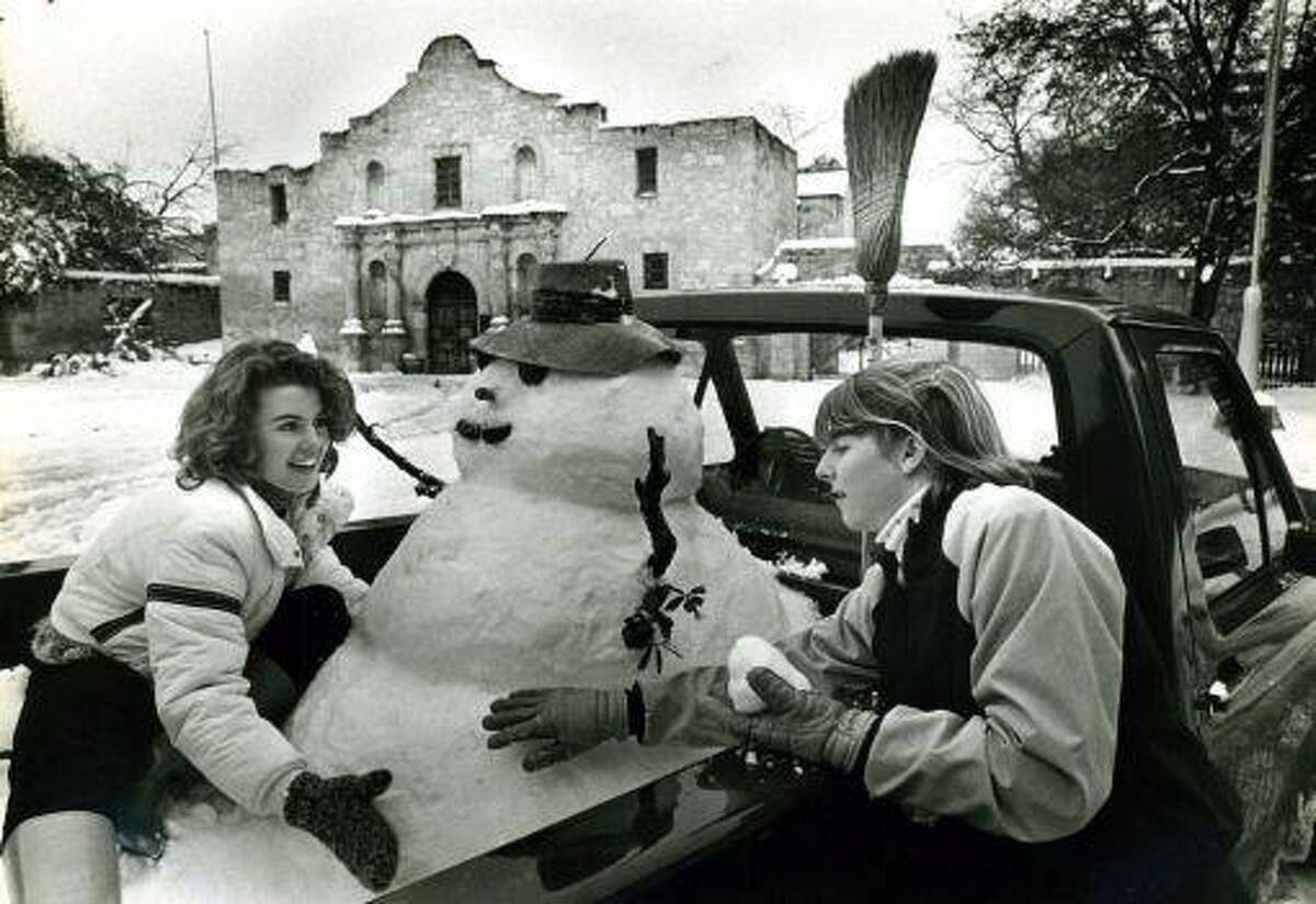 Lolly Flowers, 20, (left) and Leslie Roberts enjoy the snow at the Alamo after building a snowman in the back of a pickup truck belonging to Flowers' brother. This photo, taken nearly a decade before the short street by the Alamo church was closed to traffic, was one of the iconic images from San Antonio's record snowstorm in 1985.