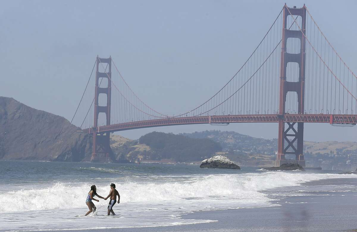 FILE - This Wednesday, June 21, 2017 file photo children play in the surf at Baker Beach with the Golden Gate Bridge shown at rear in San Francisco. Engineers will have to do more wind testing on a model of the Golden Gate Bridge before the span is modified for a seismic upgrade project and a suicide barrier. Testing done last month in a Canadian lab showed the bridge model performed well under a horizontal wind flow of more than 100 mph. But the bridge became unstable when the wind flow was changed by 1 degree. (AP Photo/Jeff Chiu,File)