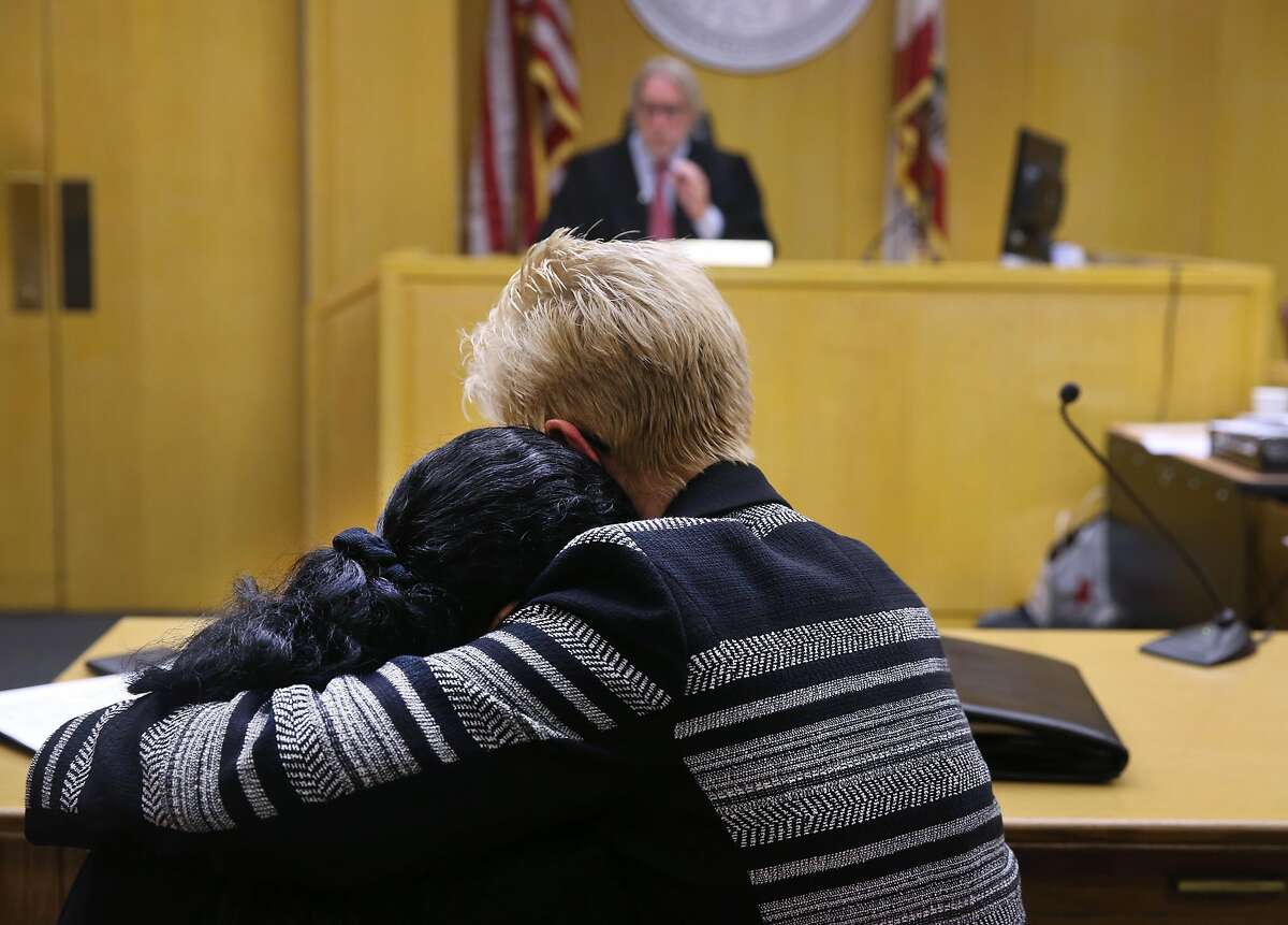 Danielle Bologna is hugged by family friend Marti McKee (right) after reading a personal statement in front of Superior Court Judge Brendan Conroy before he sentences Wilfredo Reyes to 10 years in prison in San Francisco, Calif. on Friday, July 10, 2015 for his role in the 2008 murder of Bologna's husband Anthony Bologna and their two sons Matthew and Michael in a case of mistaken identity.