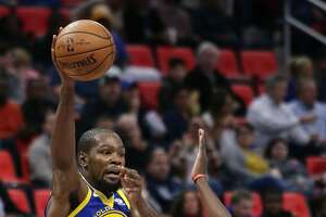 Golden State Warriors forward Kevin Durant (35) passes the ball over Detroit Pistons forward Tobias Harris (34) during the first quarter of an NBA basketball game Friday, Dec. 8, 2017, in Detroit. (AP Photo/Duane Burleson)
