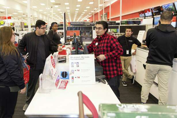An employee hands a customer a receipt after making a purchase at a Target Corp. store on Black Friday in Dallas on Nov. 24, 2017. MUST CREDIT: Bloomberg photo by Laura Buckman.