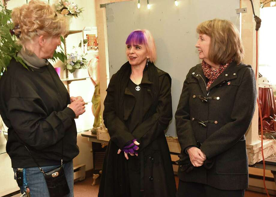 Restoration specialist Andrea Daley, left, speaks with artist Nina Stanley, center, as the Little Italy Neighborhood Quality of Life Committee unveils the former St. MaryOs Parish Restored Nativity Project at Michele's Floral Designs on Friday, Dec. 8, 2017 in Troy, N.Y. Rensselaer County Executive Kathy Jimino stands at right. (Lori Van Buren / Times Union) Photo: Lori Van Buren / 20042356A