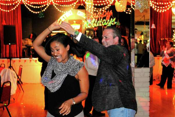 Jenny Rosario and her friend Orlando Hernandez dance during Liceo Cubano of Bridgeport's annual Coquito Contest at the club on Fairfield Ave in Bridgeport, Conn., on Friday Dec. 8, 2017. Participants sampled seven coquito creations and judged them based on things like taste, texture and alcohol content. Proceeds benefit the Puerto Rican Parade of Fairfield County.