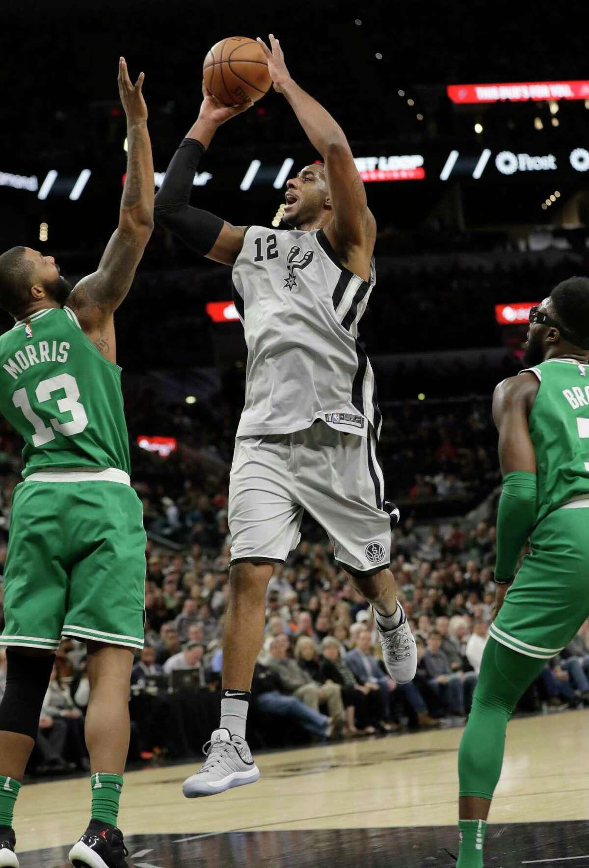 San Antonio Spurs forward LaMarcus Aldridge (12) shoots over Boston Celtics forward Marcus Morris (13) during the first half of an NBA basketball game Friday, Dec. 8, 2017, in San Antonio. (AP Photo/Eric Gay)
