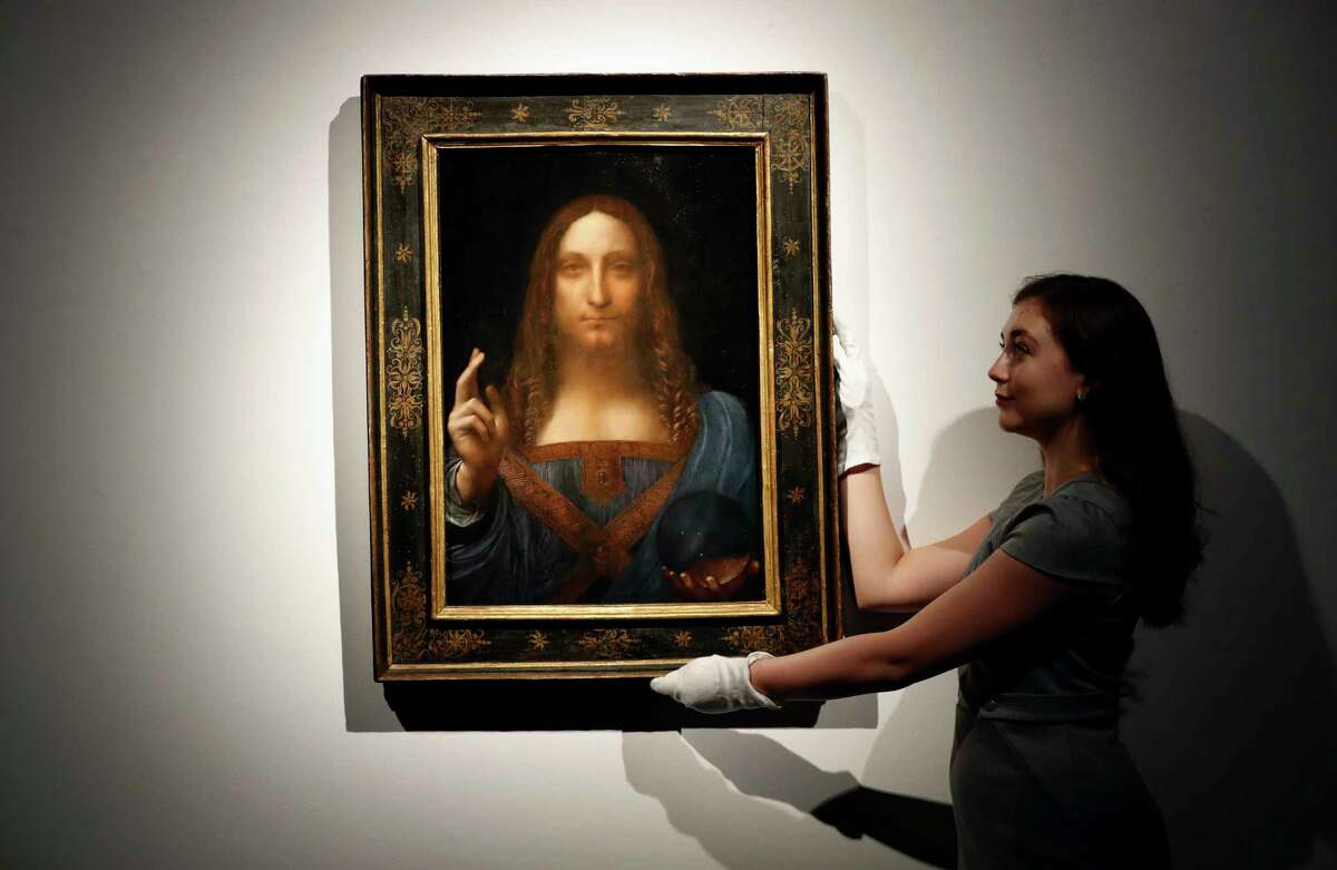 """FILE- In this Oct. 24, 2017 file photo, an employee poses with Leonardo da Vinci's """"Salvator Mundi"""" on display at Christie's auction rooms in London. The rare painting of Christ, which that sold for a record $450 million, is heading to a museum in Abu Dhabi. The newly-opened Louvre Abu Dhabi made the announcement in a tweet on Wednesday, Dec. 6. (AP Photo/Kirsty Wigglesworth, File) ORG XMIT: NYR103"""