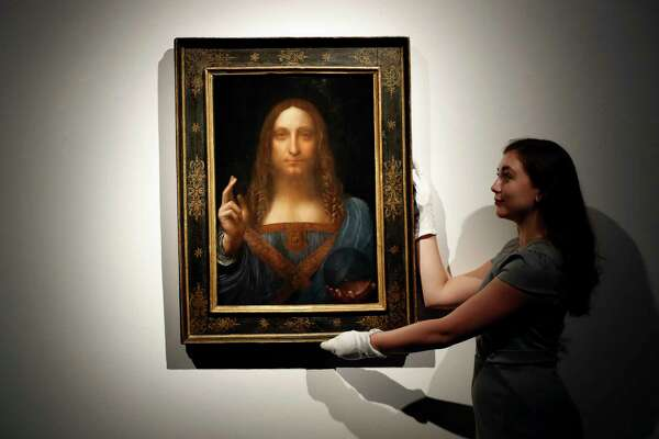 "FILE- In this Oct. 24, 2017 file photo, an employee poses with Leonardo da Vinci's ""Salvator Mundi"" on display at Christie's auction rooms in London. The rare painting of Christ, which that sold for a record $450 million, is heading to a museum in Abu Dhabi. The newly-opened Louvre Abu Dhabi made the announcement in a tweet on Wednesday, Dec. 6. (AP Photo/Kirsty Wigglesworth, File) ORG XMIT: NYR103"