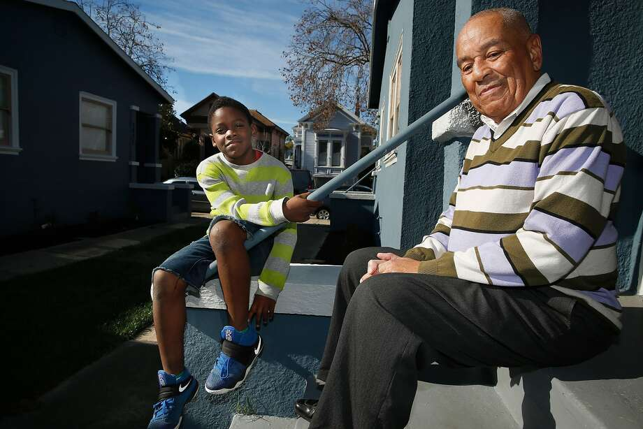 Ronald Calbert sits on the steps of his West Oakland home with his godson, Marvell Marshall, 8. Photo: Liz Hafalia, The Chronicle