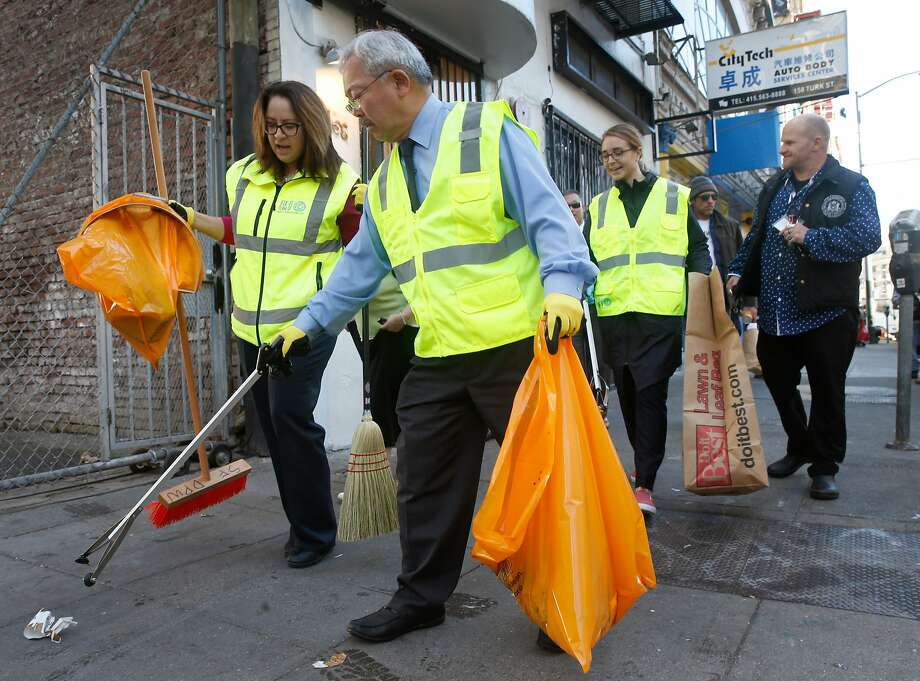 Mayor Ed Lee pitches in to help his multi agency Fix-It Team clean up Tenderloin sidewalks. The Fix-It Team carries a container for needles. Photo: Paul Chinn, The Chronicle
