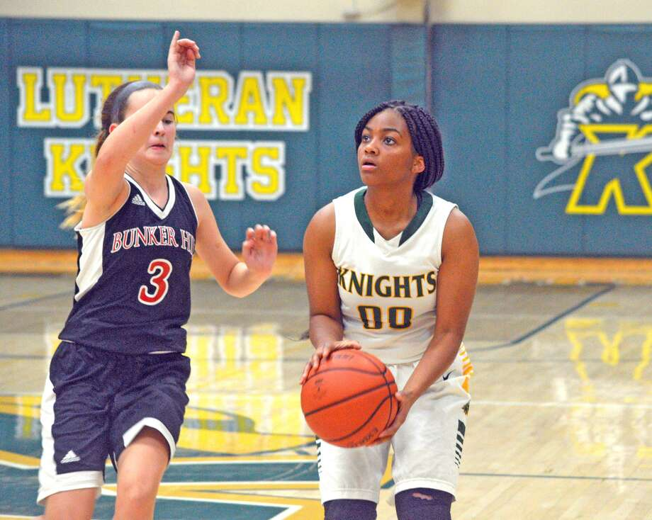 Metro-East Lutheran sophomore Destiny Williams, right, attempts a shot while being guarded by Bunker Hill's Brylie Chrisman during Friday's game at MELHS.