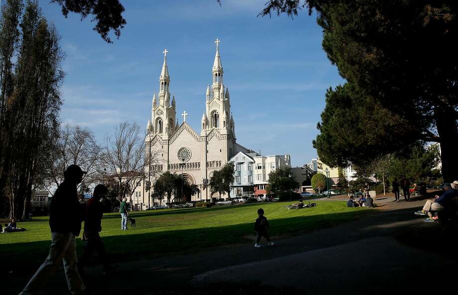 North Beach's popular Washington Square, with SS Peter and Paul's Church as a backdrop, attracts a diverse array of visitors on a sunny December day. Photo: Michael Macor, The Chronicle