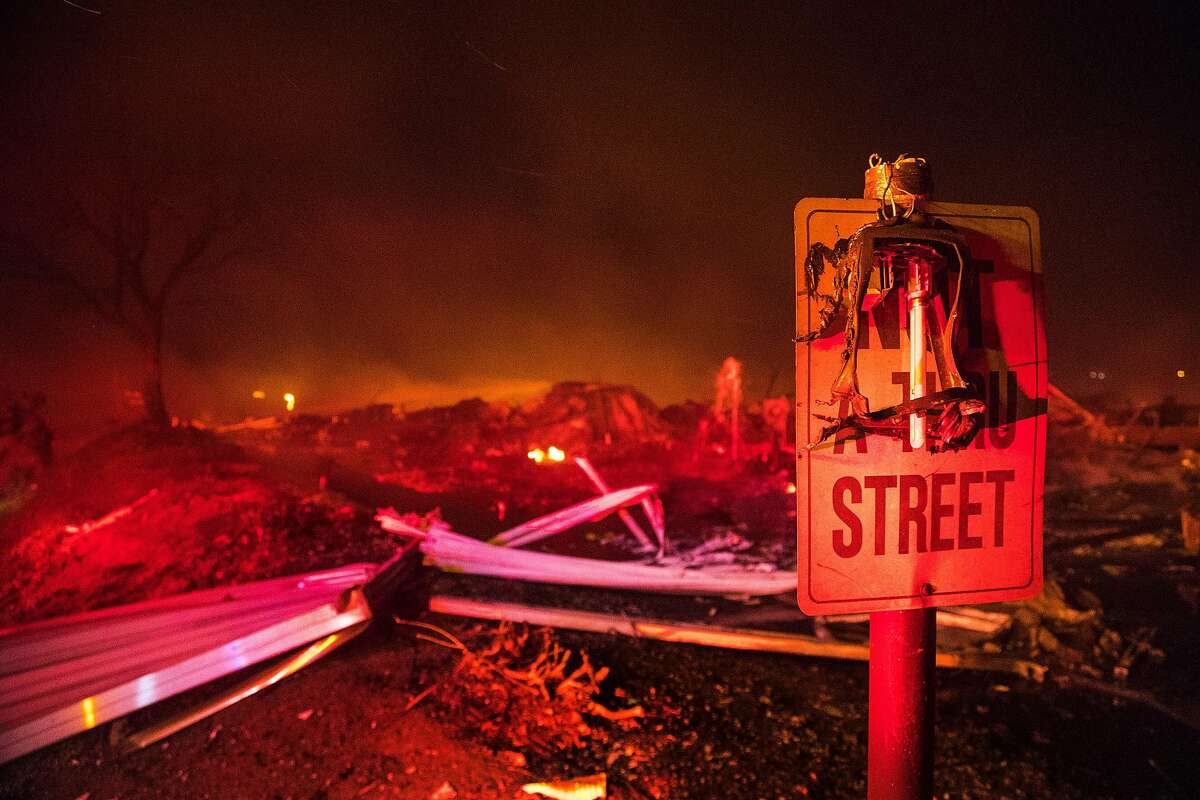 A burned street lamp hangs over a road sign in front of complete devastation after the Lilac fire burned rows and rows of mobile homes at Rancho Monserate Country Club on Dec. 7, 2017 in Pala Mesa, Calif. (Gina Ferazzi /Los Angeles Times/TNS)