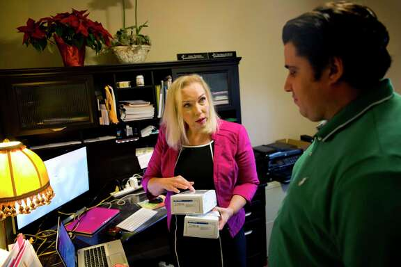Gail Trauco, owner of The PharmaKon, talks with Jordan Rubio, her office manager and son, while working in her home office in Georgia.