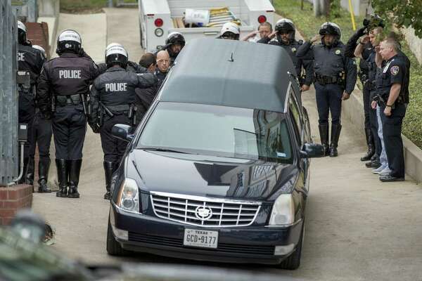 San Marcos Police Chief Chase Stapp, far right, salutes with other officers, as the body of San Marcos Police officer Kenneth Copeland is transferred to a hearse at the Travis County Medical Examiner's Office in Austin, Texas, on Tuesday Dec. 5, 2017. Copeland was killed Monday while he was serving a warrant on a suspect, according to a police statement.