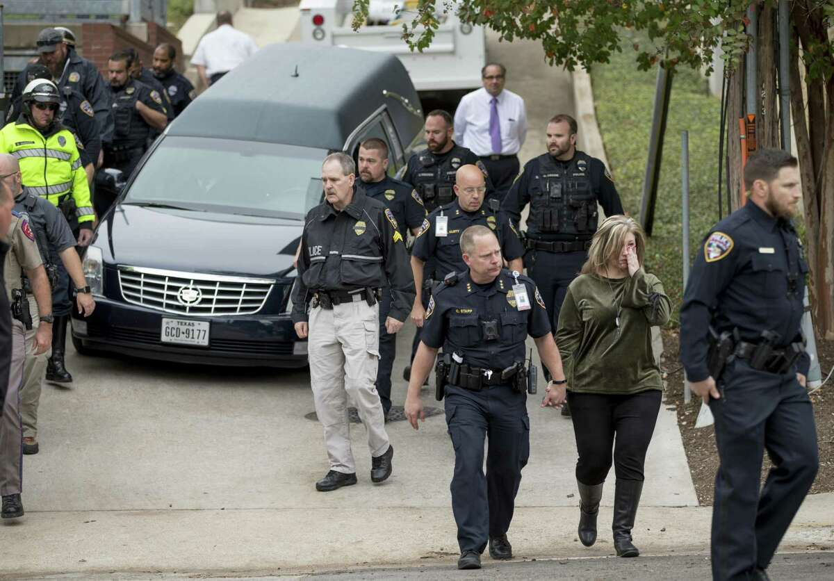 San Marcos Police Chief Chase Stapp, front, walks away after the body of San Marcos Police officer Kenneth Copeland was transferred to a hearse at the Travis County Medical Examiner's Office in Austin, Texas, on Tuesday Dec. 5, 2017. Copeland was killed Monday while he was serving a warrant on a suspect, according to a police statement