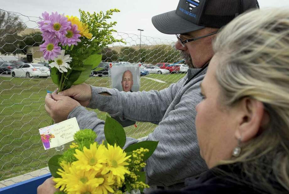 Kathleen and Chris Chomel put flowers on a memorial for slain San Marcos police officer Kenneth Copeland at Central Texas Medical Center in San Marcos, Texas, on Tuesday Dec. 5, 2017, the day after he was killed attempting to serve a warrant. (Jay Janner/Austin American-Statesman via AP) Photo: Jay Janner, MBO / Associated Press / Austin American-Statesman