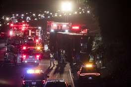 Emergency responders work at the scene of an overturned passenger bus on southbound Highway101 north of Cesar Chavez Boulevard in San Francisco, Calif. on Friday, Dec. 8, 2017.