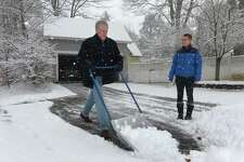 Ed Wiggers and his daughter Lucia shovel the driveway outside their home as Norwalk residents deal with the snowstorm Saturday, December 9, 2017, in Norwalk, Conn.