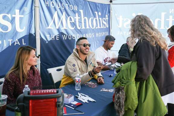 Houston Astros shortstop Carlos Correa, center, accompanied by his fiancé Daniella Rodriguez, left, and Houston Astros pitcher Michael Feliz, right, hands out autographs during a toy drive on Saturday, Dec. 9, 2017, at Houston Methodist Emergency Care Center in The Woodlands. (Michael Minasi / Houston Chronicle)