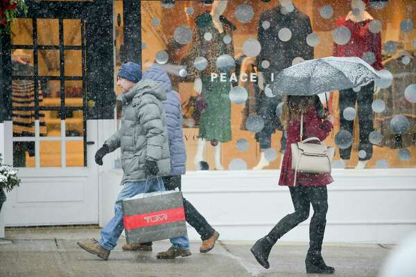 Pedestrians makes their way along Greenwich Avenue as snow from a winter storm falls  in Greenwich, Conn. on Dec. 9, 2017.