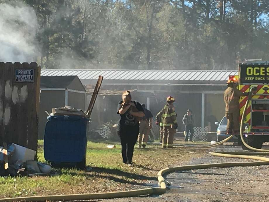 Fire crews were on scene at the 1600 block of Concord Street in Vidor Saturday battling a house fire. The homeowner is seen here exiting the home with one of her six dogs. One other dog was killed in the fire. Photo: Krista Chandler