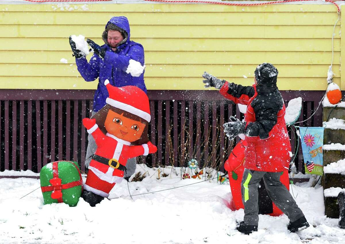 Billy Mallette, 10, throws snow at his dad's fiance Roseanne Fazzino in front of their home on Hawthorne Ave in Derby, Conn., on Saturday Dec. 9, 2017.