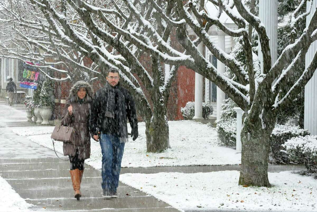 As snow falls Sam and Brittney Doorman make their way along River Street to catch the train in downtown Milford, Conn., on Saturday Dec. 9, 2017.