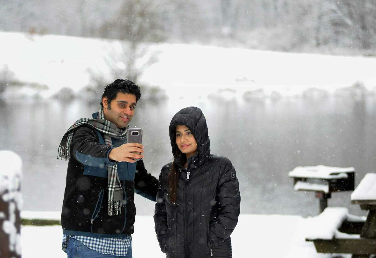 Harun Qureshi, of Naugatuck, takes selfies with his wife Annie at Osbornedale State Park in Derby, Conn., on Saturday Dec. 9, 2017. Annie recently moved from Pakistan to join her husband and this is the first time she has seen snow.