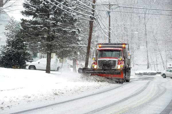 A snow plow makes its way along Howe Ave in Shelton, Conn., on Saturday Dec. 9, 2017. Original forecasts predicted double the amount of snow that actually fells in the region.
