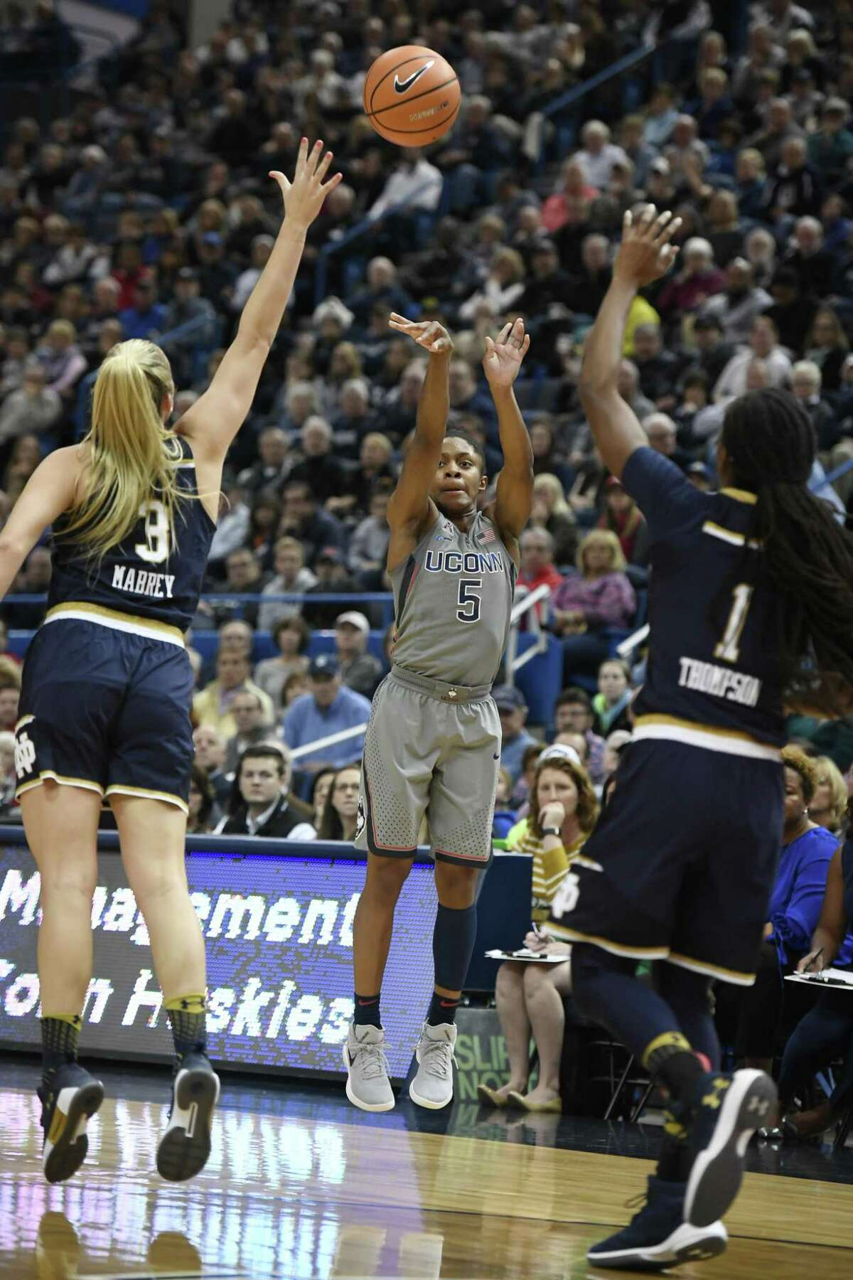 UConn's Crystal Dangerfield shoots between Notre Dame defenders Marina Mabrey, left, and Lili Thompson on Dec. 3.