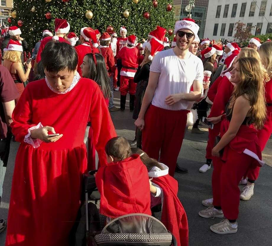 Jacky Chu (left) of San Francisco and his children join the Santa-robed thousands congregating in Union Square on Saturday to kick off the city's annual SantaCon, a day of fun and charity that combines pub-crawling with donating Toys for Tots to the Marine Corps' cause. Photo: Kevin Fagan / The Chronicle / Kevin Fagan / The Chronicle