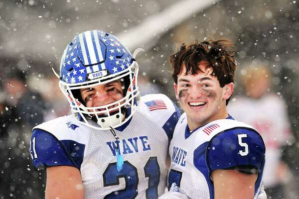 With snow falling all around them, Darien High School football players, Mitchell Pryor (#21), left, and quarterback Jack Joyce (#5) watched as the final seconds of the Class LL high school championship football game ticked off the clock giving Darien the state title as they defeated Greenwich High School, 31-22, at Boyle Stadium in Stamford, Conn., Saturday, Dec. 9, 2017.