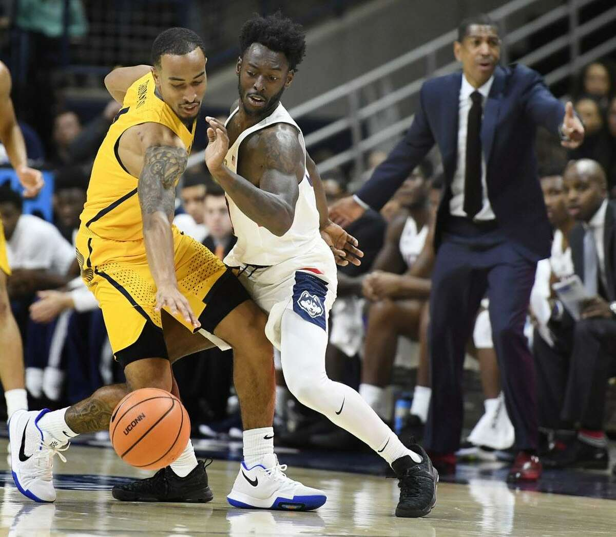 Coppin State's Tre' Thomas, left, is guarded by UConn's Antwoine Anderson, right, during the first half of an NCAA college basketball game, Saturday in Storrs.