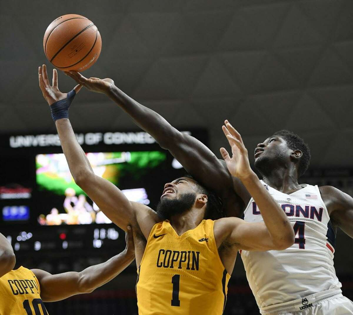Connecticut's David Onuorah, right, grabs a rebound over the head of Coppin State's Chad Andrews- Fulton, left, during the first half of an NCAA college basketball game, Saturday, Dec. 9, 2017, in Storrs.