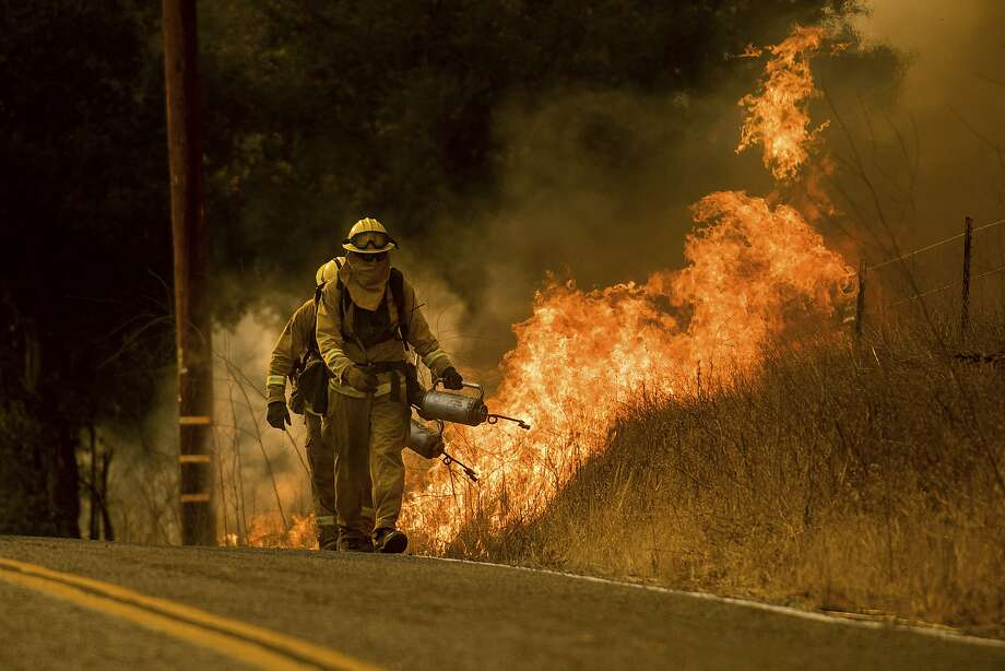 Firefighters light a backfire while trying to keep a wildfire from jumping Santa Ana Road near Ventura on Dec. 9. Photo: Noah Berger, Associated Press